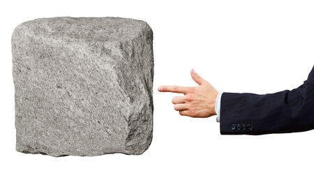 metaphorical: Businessman in suit pointing at huge stone
