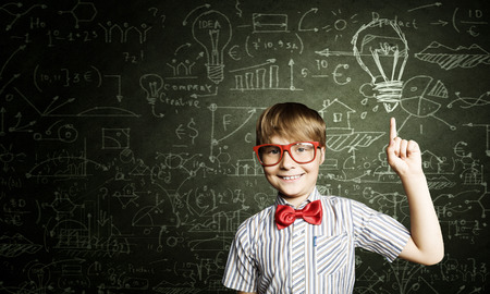 Genius boy in red glasses near blackboard with formulas Banco de Imagens