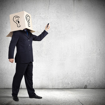 acknowledge: Businessman using mobile phone wearing carton box on head