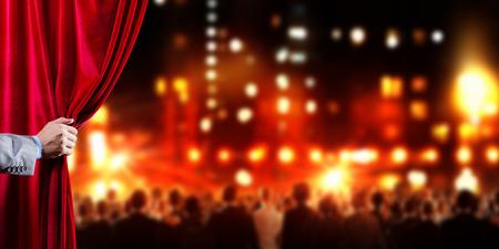 赤いベルベットのカーテンを開くのビジネスマンの手 写真素材