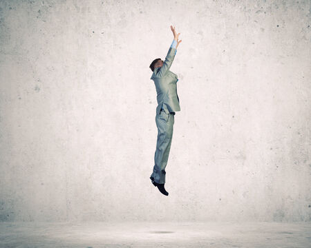 Young businessman jumping up trying to reach goal photo