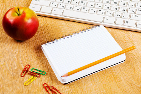 Red apple notepad and keyboard on wooden table photo