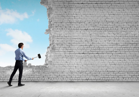 cement solution: Young determined businessman breaking wall with hammer Stock Photo