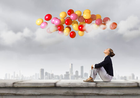 Young pretty businesswoman sitting on top of building with colorful balloons flying above photo