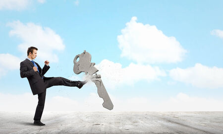 wayout: Angry businessman crashing stone key with kick Stock Photo