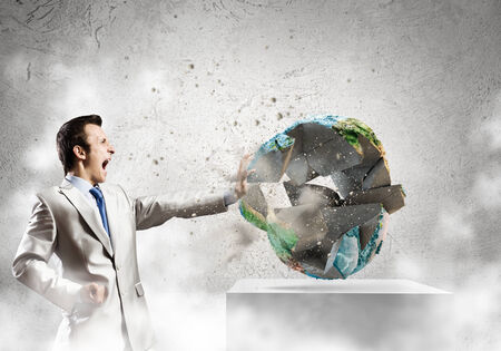 Young determined businessman crashing Earth planet with punch  Elements of this image are furnished by NASA photo