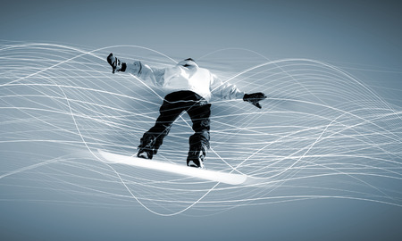 Male snowboarder making jump against media background photo