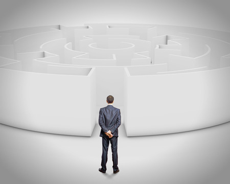 businessman standing: Successful businessman standing near the entrance of labyrinth