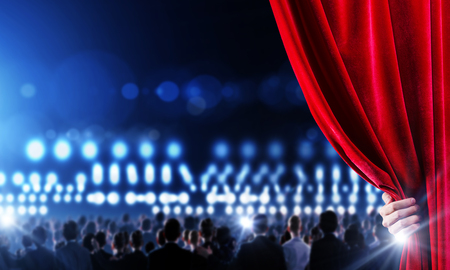 opulent: Hand of businessman opening red velvet curtain