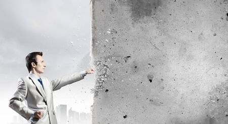 frenzy: Businessman breaking stone wall with karate punch
