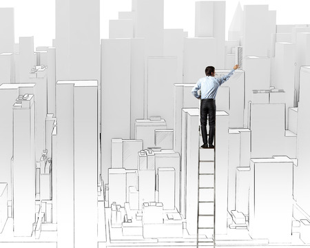 Rear view of businessman standing on ladder and drawing project photo