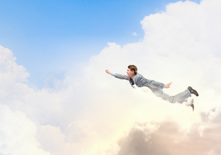 Young businessman superhero flying high in sky photo