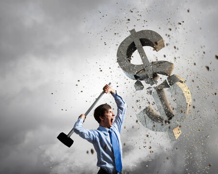 Young businessman crashing with hammer stone dollar symbol photo