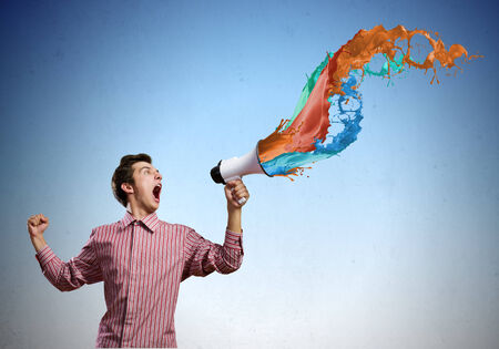 Young man in casual screaming in megaphone photo