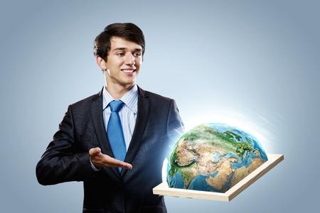 protecting your business: Apuesto hombre de negocios la celebraci�n de marco con el planeta Tierra Elementos de esta imagen son proporcionados por la NASA Foto de archivo