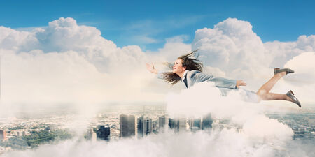 Young determined businesswoman flying high in sky Stock Photo