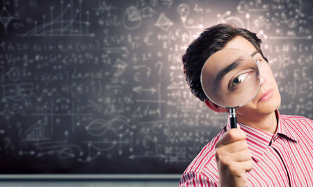 Young man scientist looking in magnifying glass photo