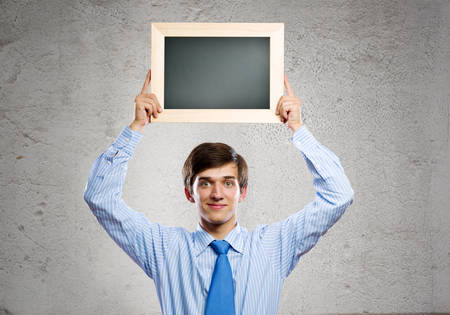Handsome businessman holding blank frame  Place for text photo