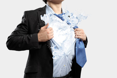powerful creativity: Businessman in suit tearing his shirt on chest