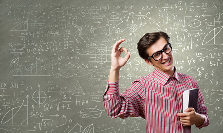 Young funny man in glasses against chalk blackboard photo