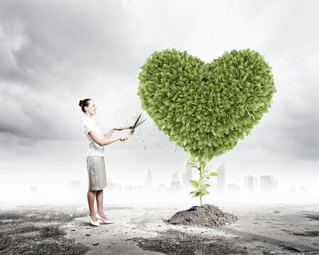 Young attractive businesswoman cutting lawn in shape of heart photo