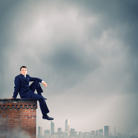 Young businessman sitting on roof of building photo