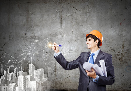 Young man engineer in helmet drawing construction project photo
