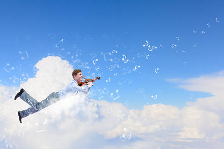Young businessman flying in sky and playing violin photo