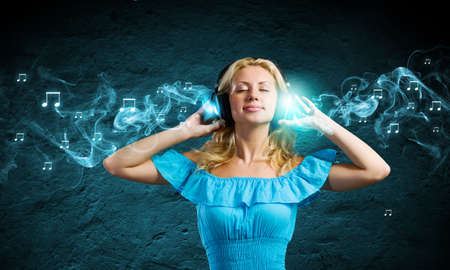 Young blond girl in blue dress listening music photo