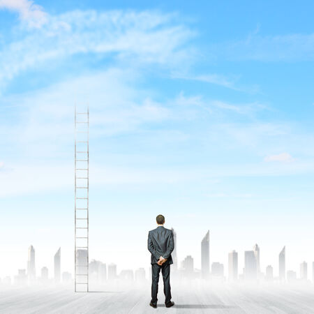 Rear view of businessman standing near ladder going high in sky photo