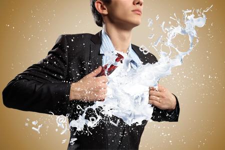 Businessman acting like superhero tearing shirt on chest Stock Photo