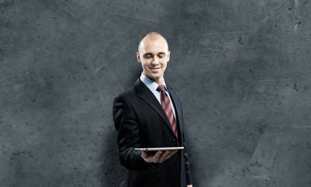 Young businessman against grey background holding tablet pc photo