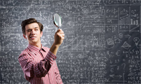 Young man in casual looking in magnifier photo