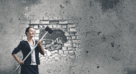 Young attractive businesswoman with hammer in hands photo