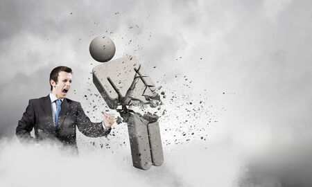 opponent: Angry young businessman fighting with stone opponent Stock Photo