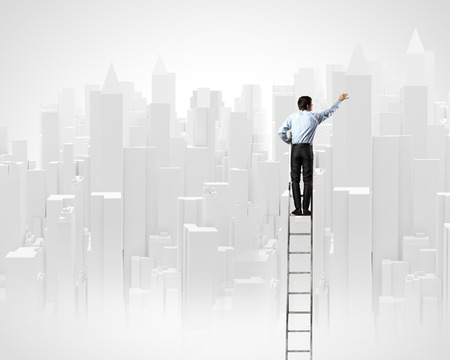 businessman standing: Rear view of businessman standing on ladder and drawing project Stock Photo