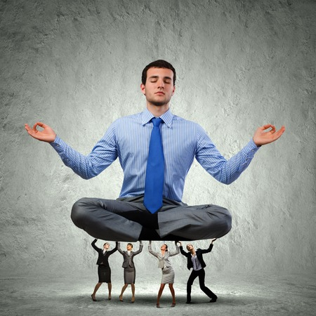 Young businessman sitting in lotus pose and supported by colleagues photo