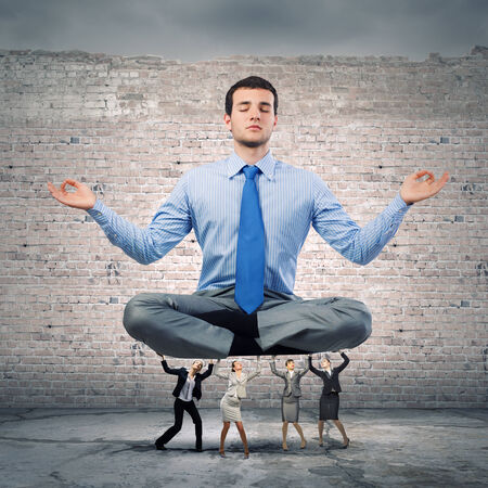 meditation help: Young businessman sitting in lotus pose and supported by colleagues