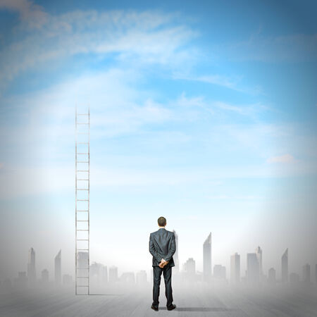 businessman standing: Rear view of businessman standing near ladder going high in sky Stock Photo