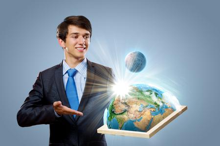 protecting your business: Bastidor de sujeci�n Apuesto hombre de negocios con el planeta Tierra