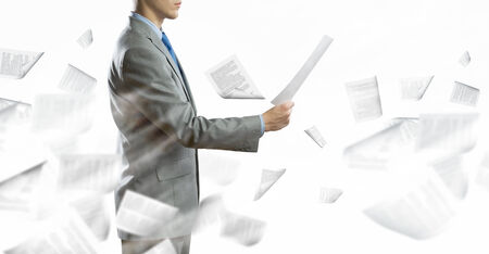 businessman signing documents: Back view of businessman reading documents in hand Stock Photo