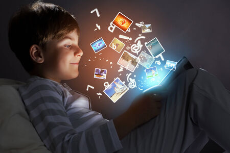 parental control: Little cute boy sitting in bed and using tablet