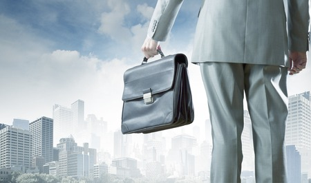 Back view of businessman with suitcase in hand photo