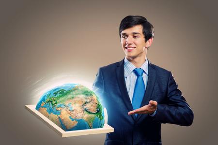 protecting your business: Apuesto hombre de negocios la celebraci�n de marco con la Tierra planeta elementos de esta imagen proporcionada por la NASA est�n