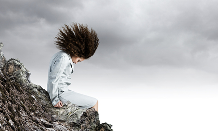 atop: Young businesswoman with waving hair sitting on top of mountain Stock Photo