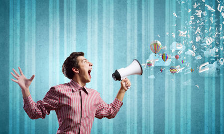 Young man in casual screaming in megaphone Stock Photo