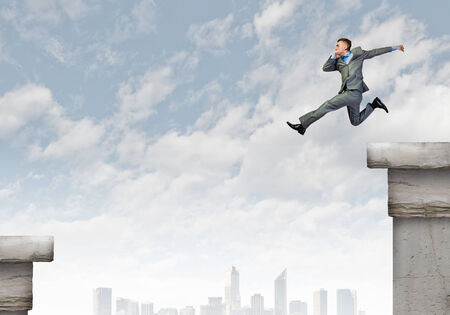 Young businessman jumping over gap  Risk concept photo