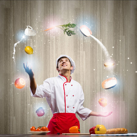 Young man at kitchen juggling with ingredients photo