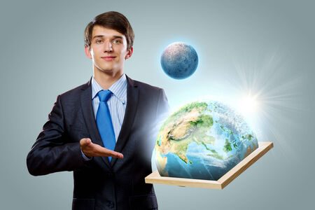 Handsome businessman holding frame with Earth planet  photo