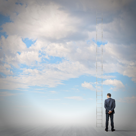 Rear view of businessman standing near ladder going high in sky Stock Photo